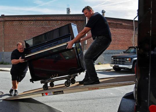 tungt piano flyttas upp för flyttbil