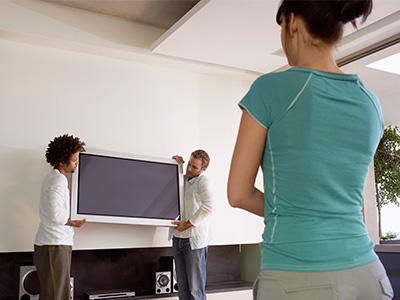 tre personer flyttar en tung tv-apparat